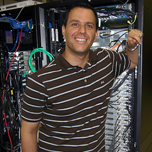 Photo of Dr. Andres Cisneros, UNT computational chemist, in front of a computer tower