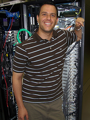Dr. Andres Cisneros standing in front of a computer tower.
