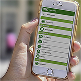 Photo of a hand holding a smartphone with the UNT mobile app on the screen.