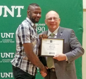 DaMiri Young pictured shaking hands with UNT Vice President Bob Brown